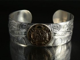 Native Wolves carved into a .925 Silver Bracelet with 14k Gold Sun by William Cook
